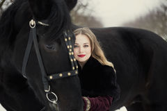 Girl in dark clothes with a black horse stock photography