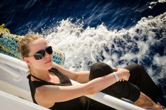 A girl in dark clothes and  rests on a white yacht Royalty Free Stock Photos