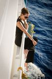 A girl in dark clothes and  rests on a white yacht Stock Images