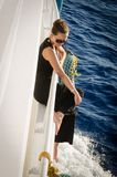 A girl in dark clothes and  rests on a white yacht Stock Photos
