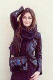 Girl in a dark clothes standing near light wall Stock Photos