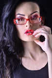 Girl with dark curly hair, makeup, red glasses Stock Image