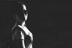 The girl in dark glasses on a dark background, the silhouette of the girl in sunglasses, Stock Image