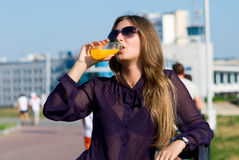Girl in dark glasses drinks orange drink Stock Photo