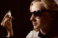 The girl in dark glasses holding a watch on a chain. Stock Images