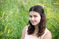 The girl with dark hair on background of green grass Stock Photography