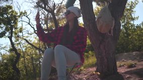 A girl with dark hair in a black and red shirt, a bandana and glasses sits in the forest, takes a photo on the phone. stock video