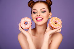 Girl with dark hair and bright makeup holding sweet donuts Royalty Free Stock Photos