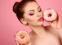 Girl with dark hair and bright makeup holding sweet donuts Stock Image