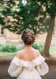 Girl with dark hair and delicate skin shows gorgeous hairstyle from large number of braids, lady stands with her back to. Camera in white dress with open back stock images