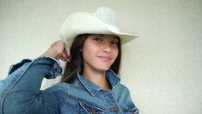 Girl with dark hair in denim jacket and in white cowboy hat. Pretty girl teenager with loose dark hair in denim jacket and white cowboy hat stands against wall stock footage