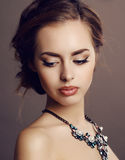 Girl with dark hair and evening makeup with luxurious necklace Stock Photography