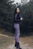 Girl with dark hair in the forest. She wears a black leather jacket and gray jeans. A woman of model appearance stylishly dressed Stock Photo