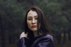 Girl with dark hair in the forest. She wears a black leather jacket. Portrait of a smiling girl with freckles Royalty Free Stock Photography