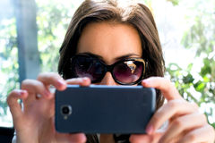 Girl with dark hair and glasses taking a selfie Royalty Free Stock Photos