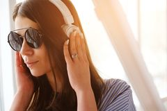A girl with dark hair in headphones listening to music, sitting in a room, airport, office. A young woman with glasses. And a light shirt. Close up stock images