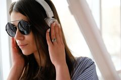 A girl with dark hair in headphones listening to music, sitting in a room, airport, office. A young woman with glasses and a light stock photo