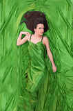Girl with dark hair lying on green. Beautiful girl with long dark hair lying on green silk royalty free stock images