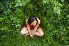 The girl with dark hair sits on a green grass Royalty Free Stock Photos