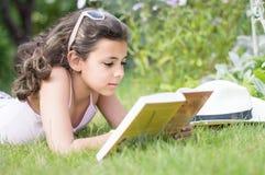 Girl with dark hair sitting on the doorstep in the garden Stock Photos