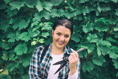 Girl With Dark Hair And Trimmer with Vine Behind Stock Photography