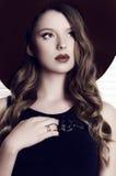 Girl with dark hair wearing black dress and elegant hat Royalty Free Stock Image
