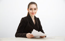 Girl in dark jacket holding a stack of documents. Royalty Free Stock Images