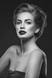 Girl with dark lips and hairdo. Beautiful young woman with dark lips and stylish hairdo. Beauty shot over dark grey background. Copy space Royalty Free Stock Images