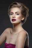 Girl with dark lips and hairdo. Beautiful young woman with dark lips and stylish hairdo. Beauty shot over dark grey background. Copy space Stock Image
