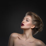Girl with dark lips and hairdo. Beautiful young woman with dark lips and stylish hairdo. Beauty shot over dark grey background. Copy space. Square composition Royalty Free Stock Photo