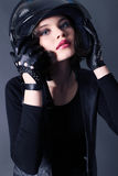 Girl with dark short hair wears biker clothes. leather jacket and helmet Stock Photography