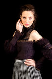 Girl in dark Victorian dress with hand besides her eyes Stock Photo