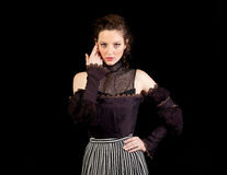 Girl in dark Victorian dress. Girl in a dark Victorian dress with looking in the camera and holding her hand besides her eye on a black background Stock Images