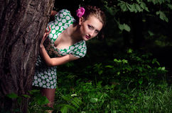 Girl in dark wood. Peeking out from behind a tree stock photography