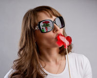 Girl on a date kisses candy in the shape of a heart, symbol of l Stock Photo