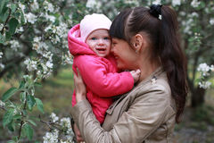 Girl with daughter in a spring apple garden Stock Photo