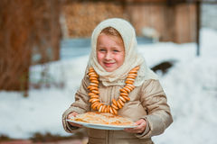 Girl on the day of the carnival treats pancakes Royalty Free Stock Photography