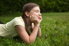 Girl day dreaming in nature. Portrait of a little girl day dreaming outdoors in nature royalty free stock photos