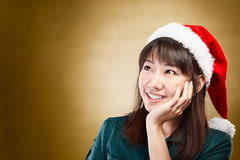 Girl daydreaming about  Christmas. Asian lady using santa hat daydreaming about Christmas Stock Image
