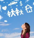 Girl daydreaming with family and household clouds on blue sky Royalty Free Stock Images