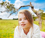 Girl daydreaming in a field Stock Photography