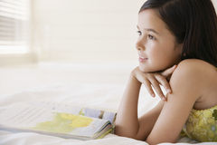 Girl Daydreaming While Reading Book Stock Photo