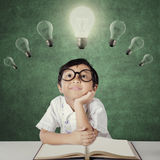 Girl daydreaming under lightbulb in class Stock Image