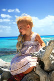 Girl on a dead tree. Baby girl on a dead tree at tropical beach Royalty Free Stock Photos