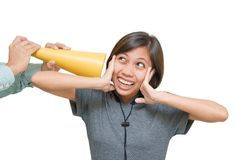 Girl deafened by horn. Portrait of an Asian girl deafened by a too loud horn and covering her ears with an overloaded terrified facial expression. Isolated over Stock Photo