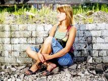 Girl in debris. Sitting girl profile in debris Stock Photo