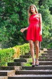 Girl before the Debutante Ball. Down stairs with red dress Stock Photography