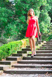 Girl before the Debutante Ball. Down stairs with red dress Stock Photos