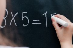 The girl decides an example in mathematics. On the desk Stock Image