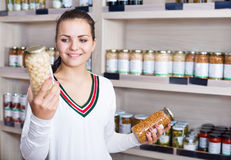 Girl deciding on canned beans. Smiling girl deciding on canned beans in the grocery shop Stock Images
